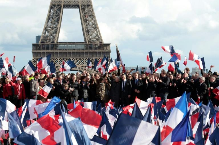 French presidential election candidate for the right-wing Les Republicains party Francois Fillon (C), flanked by his wife Penelope Fillon and his daughter Marie Fillon, acknowledges the crowd as he stands on stage near the Eiffel Tower