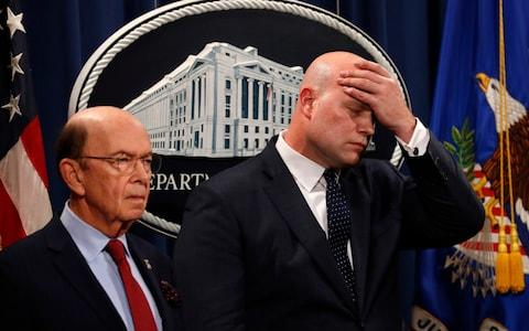 Acting Attorney General Matt Whitaker, right, wipes his brow after announcing the indictments. On the left is Commerce Secretary Wilbur Ross - Credit: AP