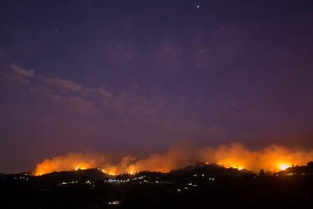 Flames and smoke from a forest fire are seen in the village of Moya in the Canary Island of Gran Canaria