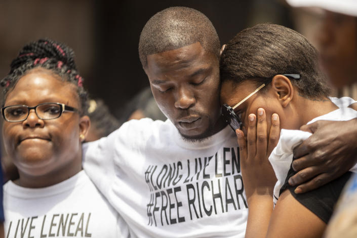 From left, Cheryl Frazier, sister of Leneal Frazier; Orlando Frazier, brother of Leneal; and Jamie Bradford, 20, daughter of Leneal, embrace one another during a news conference outside of City Hall, Friday, July 9, 2021, in Minneapolis. Leneal Frazier was killed earlier in the week after his vehicle was struck by a squad car that police said was pursuing another driver linked to several robberies. Frazier was not involved in the pursuit. (Antranik Tavitian/Star Tribune via AP)