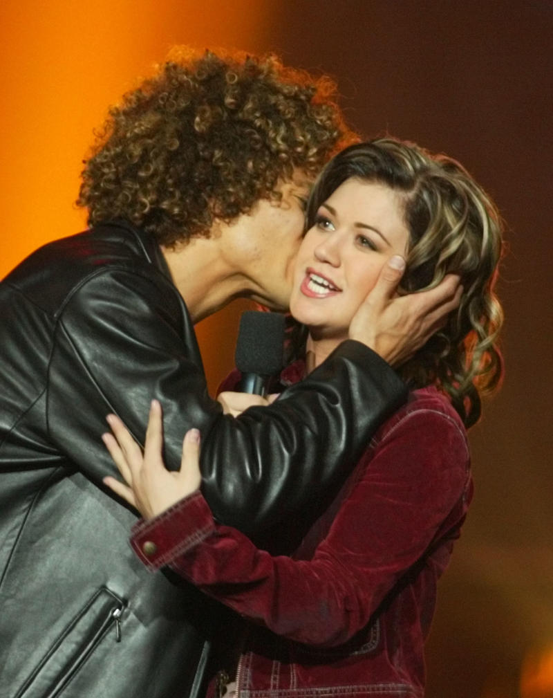 "Finalist Justin Guarini (L) kisses Kelly Clarkson, 20, of Burleston, Texas after she was named the winner in the competition of the television reality music program ""American Idol,"" September 4, 2002 at the Kodak Theatre in Hollywood. Viewers phoned in their votes after the September 3 sing-off between Clarkson and Guarini. Clarkson wins a recording contract and will also tour the country performing with the other ""American Idol"" contestants. The contestants reunite for a television special ""American Idol"" in Las Vegas which will be telecast September 23. REUTERS/Fred Prouser FSP"