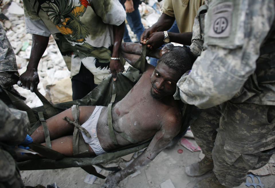 <p>Rico Dibrivell, 35, is attended by a U.S. military rescue team after being freed from the rubble of a building in Port-au-Prince, Haiti, Jan. 26, 2010. (Photo: Eduardo Munoz/Reuters) </p>