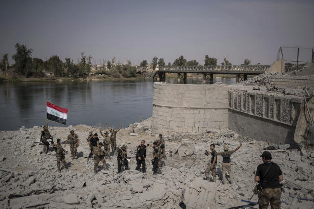 FILE - In this July 9, 2017, file photo, Iraqi Special Forces soldiers celebrate after reaching the bank of the Tigris river, in the Old City of Mosul, Iraq. (AP Photo/Felipe Dana, File)