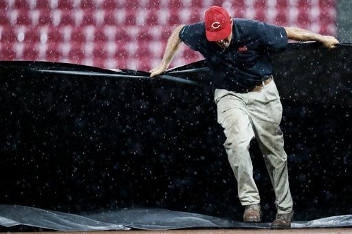 A member of the grounds crew helps pull a tarp onto the infield during a rain delay in the third inning of a baseball game between the Cincinnati Reds and the Kansas City Royals, Tuesday, Sept. 25, 2018, in Cincinnati. (AP Photo/John Minchillo)