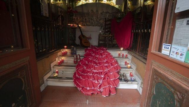 A flamenco dress, dancing shoes, a guitar and candles are laid out in the entrance of the Villa Rosa Tablao flamenco venue during a protest in Madrid, Spain. Photo credit: AP Photo/Paul White