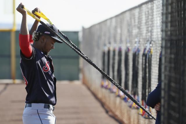 FILE - In this Feb. 14, 2020, file photo, Cleveland Indians pitcher Emmanuel Clase stretches during spring training baseball workouts for pitchers and catchers in Avondale, Ariz. The hard-throwing Clase, who was acquired this winter from Texas in the trade for two-time Cy Young winner Corey Kluber, experienced upper arm discomfort following a bullpen session last week. He continued to have issues this week and the Indians had him undergo tests Wednesday, Feb. 26, 2020. An MRI confirmed a moderate strain of the teres major muscle in his upper back. The team said he will be re-evaluated weekly, but the x-year-old is expected to miss 8-to-12 weeks of game activity.(AP Photo/Ross D. Franklin, File)