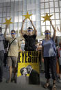 "Protesters hold European Union stars and keep their eyes closed behind a poster showing German Chancellor Angela Merkel and Bulgarian Prime Minister Boyko Borissov in front of the German Embassy in Sofia, Bulgaria, Wednesday, Aug. 12, 2020. Several hundred anti-government protesters gathered on Wednesday in front of Germany's embassy in Sofia, calling on Berlin and Brussels to ""open their eyes"" to widespread corruption in Bulgaria. During the peaceful protest, dubbed ""Eyes Wide Shut,"" organizers complained that the European Union has willfully ignored the state of affairs in its poorest member state. (AP Photo/Valentina Petrova)"
