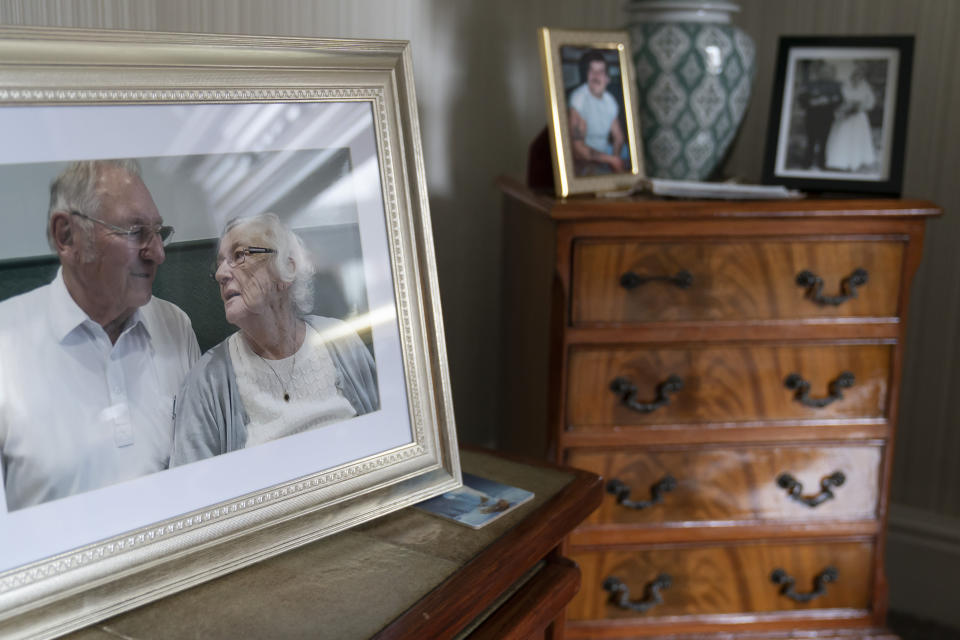"A photo of retired Gordon Bonner with his late wife Muriel on display in his home in Leeds, England, Saturday Jan. 23, 2021. For nine months, Bonner has been in the ""hinterlands of despair and desolation"" after losing Muriel, his wife of 63 years, to the coronavirus pandemic that has now taken the lives of more than 100,000 people in the United Kingdom. (AP Photo/Jon Super)"