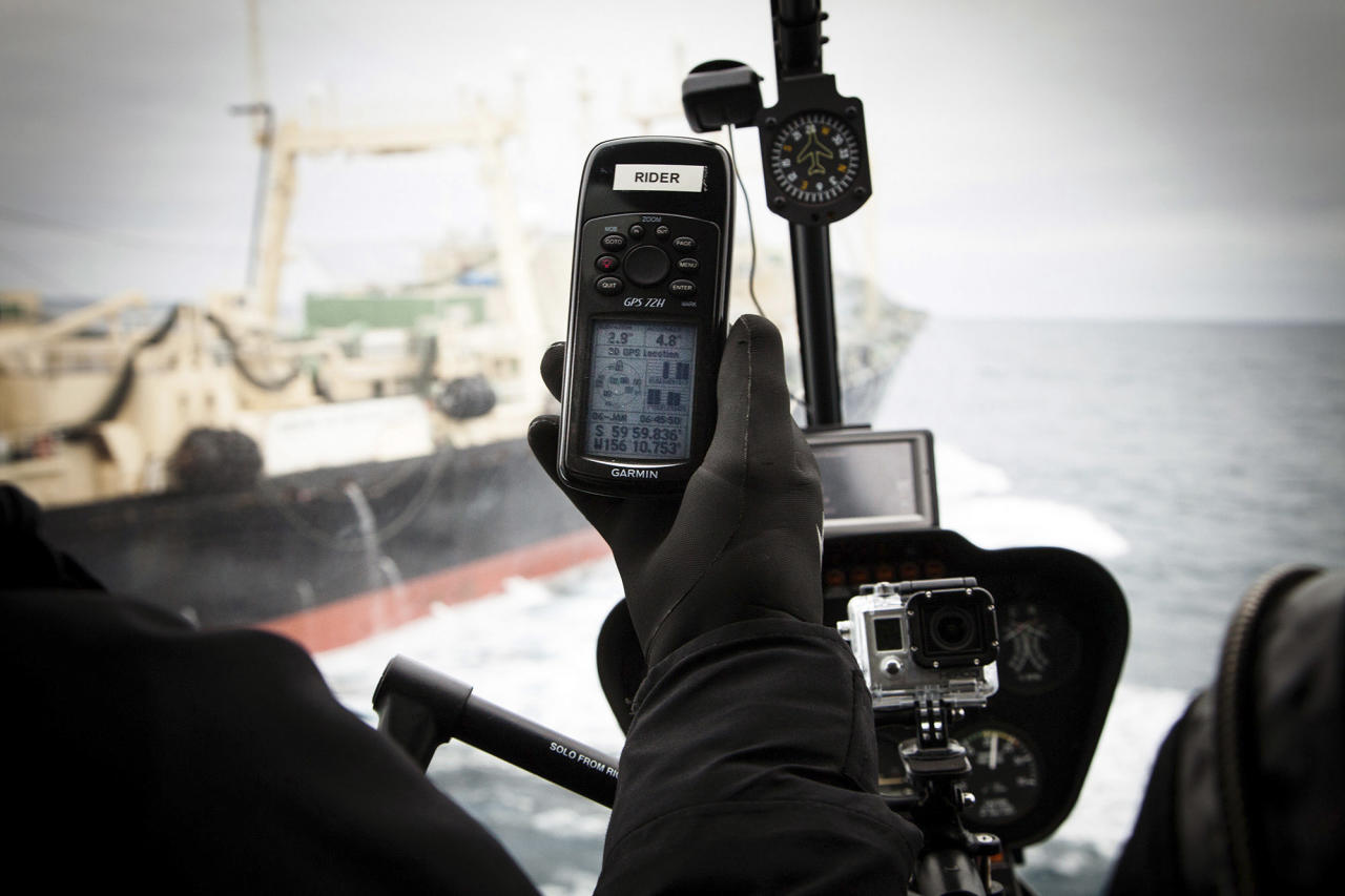 Japanese whaling ship Nisshin Maru is pictured in the background as a GPS unit in a helicopter shows the 60 degree South latitude exclusion zone from an internationally recognised whale sanctuary, in this handout picture provided by the Sea Shepherd Australia Antarctic whale defense campaign dated January 6, 2014. REUTERS/Eliza Muirhead/Sea Shepherd Australia/Handout via Reuters (ANTARCTICA - Tags: ANIMALS POLITICS) ATTENTION EDITORS - THIS IMAGE WAS PROVIDED BY A THIRD PARTY. FOR EDITORIAL USE ONLY. NOT FOR SALE FOR MARKETING OR ADVERTISING CAMPAIGNS. NO SALES. NO ARCHIVES. THIS PICTURE IS DISTRIBUTED EXACTLY AS RECEIVED BY REUTERS, AS A SERVICE TO CLIENTS