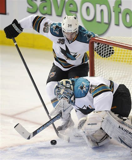 San Jose Sharks' Logan Couture (39) clears an Edmonton Oilers shot away from goalie Antti Niemi during the first period of an NHL hockey game in Edmonton, Alberta, on Monday, March 12, 2012. (AP Photo/The Canadian Press, John Ulan)