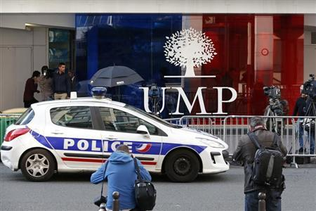 A police car passes in front of the headquarters of France's centre-right UMP political party in Paris