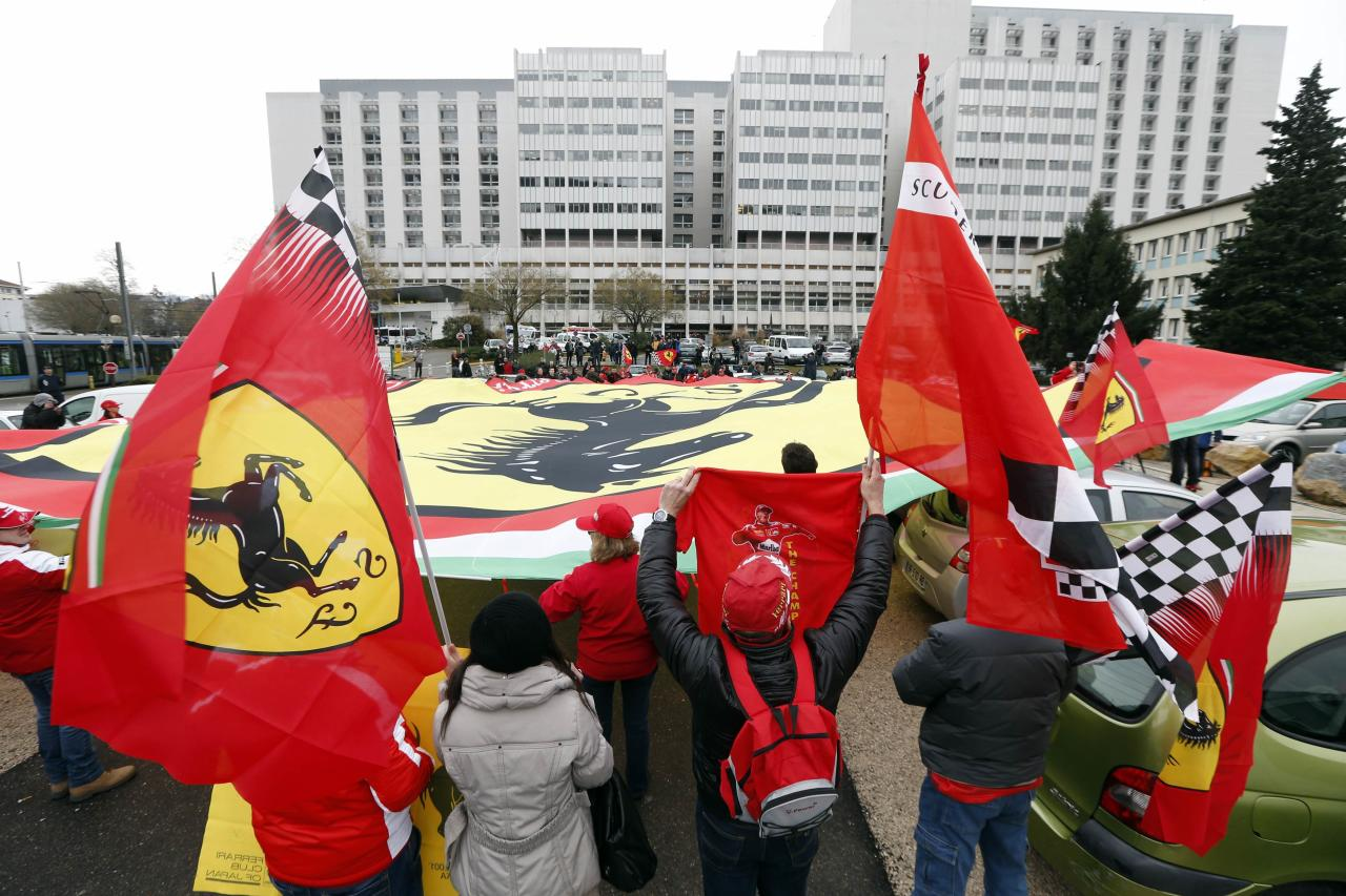 Ferrari fans from France, Italy and Germany attend a silent 45th birthday tribute to seven-times former Formula One world champion Michael Schumacher in front of the CHU hospital emergency unit in Grenoble