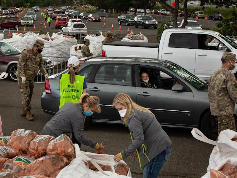 Volunteers and members of the Washington Air National Guard's 194th Wing load bags of potatoes into cars during a potato giveaway on May 14 in Tacoma. The Washington Potato Commission gave away 200,000 pounds of potatoes as farmers face reduced demand.