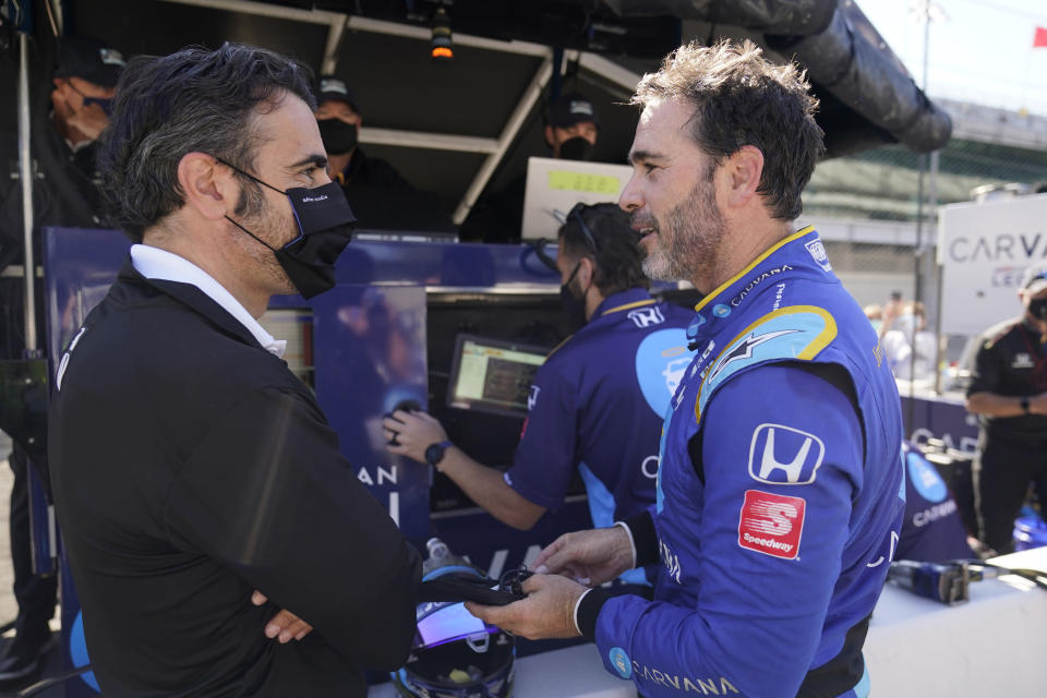 Jimmie Johnson talks with Dario Franchitti, left, following a practice session for the IndyCar auto race at Indianapolis Motor Speedway, Friday, May 14, 2021, in Indianapolis. (AP Photo/Darron Cummings)