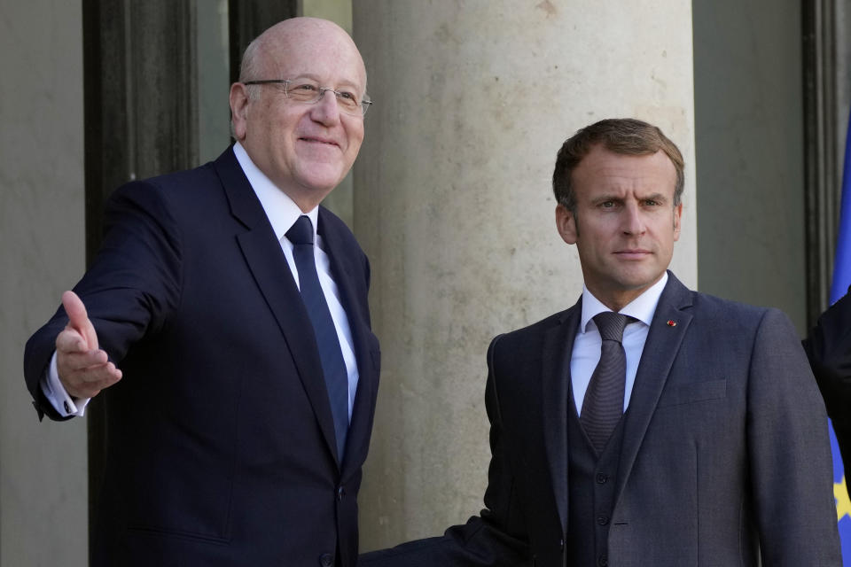 French President Emmanuel Macron, right, welcomes Lebanese Prime Minister Najib Mikati prior to their meeting at the Elysee Palace, in Paris, Friday, Sept. 24, 2021. (AP Photo/Francois Mori)