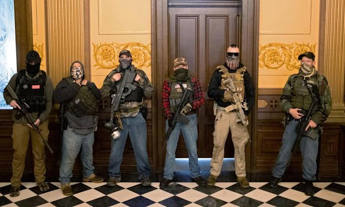 """<span class=""""element-image__caption"""">A militia group stands in front of the governor's office at the state capitol in Lansing, Michigan, on 30 April.</span> <span class=""""element-image__credit"""">Photograph: Seth Herald/Reuters</span>"""