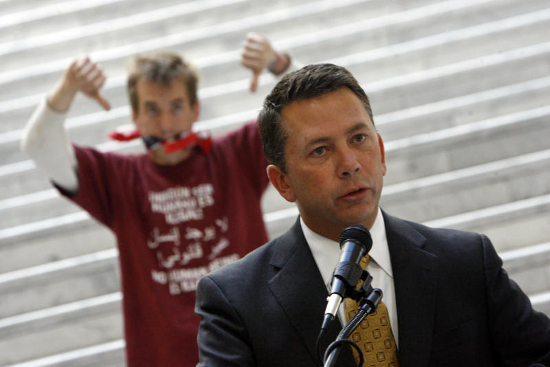 FILE - In this Aug. 13, 2010 file photo, protestor John Osburn, rear, expresses his discontent as Rep. Stephen Sandstrom, R-Orem, presents his immigration bill at the Utah State Capitol in Salt Lake City. Utah lawmakers passed the strict law confident it wouldn't end up in the same legal tangle as Arizona's, but a Federal judge has blocked the law that called for police to check the immigration status of those detained for serious crimes. Other states are keeping watch as they all try to address the problem of illegal immigration without federal intervention. (AP Photo/The Salt Lake Tribune, Francisco Kjolseth)