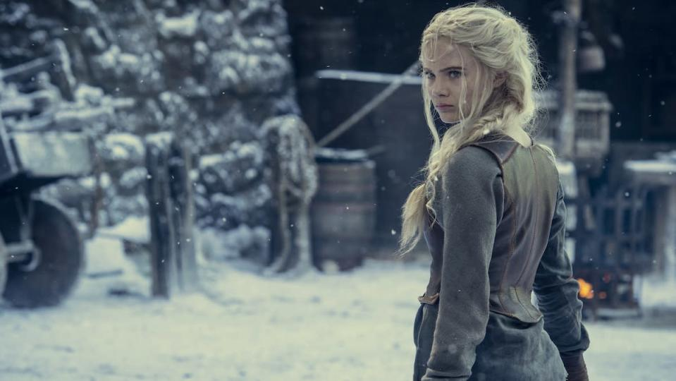A young blonde girl stands in a snowy outdoor area in a castle