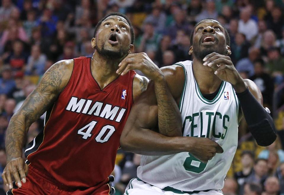 Miami Heat forward Udonis Haslem (40) and Boston Celtics forward Jeff Green (8) lock arms as they fight for position during a free throw in the first quarter of an NBA basketball game in Boston Wednesday, March 19, 2014. (AP Photo/Elise Amendola)