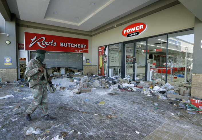 A patrolling soldier looks on at damaged stores at a shopping centre in Soweto near Johannesburg, Tuesday July 13, 2021 as ongoing looting and violence continues. South Africa's rioting continued Tuesday with the death toll rising to 32 as police and the military struggle to quell the violence in Gauteng and KwaZulu-Natal provinces. The violence started in various parts of KwaZulu-Natal last week when Zuma began serving a 15-month sentence for contempt of court. (AP Photo/Themba Hadebe)