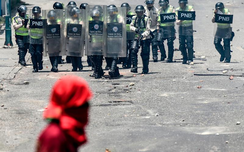 A man in a red bandanna faces off against a dozen riot police - Credit: Juan Barreto/AFP/Getty Images
