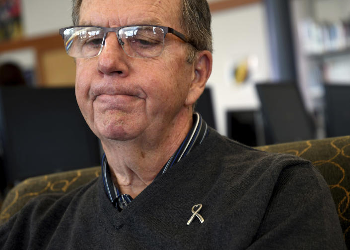 In this Saturday, March 23, 2019 photo, Rick Townsend reflects about the upcoming 20th anniversary of the mass shooting at Columbine High School in suburban Denver. Townsend's daughter, Lauren, was killed in the April 20, 1999, attack. Several survivors and family members of the victims gathered at the school's library to speak to the media Saturday. (AP Photo/Thomas Peipert)