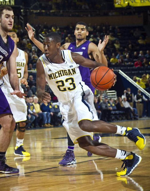 Michigan guard Caris LeVert (23) drives to the basket in the first half of an NCAA college basketball game against Northwestern at Crisler Center in Ann Arbor, Mich., Sunday, Jan. 5, 2014. (AP Photo/Tony Ding)