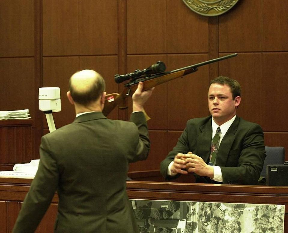 Andy Hulette, right, a former roommate of Shane Ragland, who is on trial for the murder of Trent DiGiuro, a University of Kentucky football player in July 1994 testified in the trial that enter it's third week in Fayette Circuit Court on Monday, March 25, 2002. Hullett testified that Ragland had told him about the events on the night of the murder when a party to celebrate DiGiuro's upcoming 21st birthday was taking place a couple of doors from where they lived. Hulette identified the rifle, believed to have been used, as Fayette Commonwealth's Attorney Ray Larson held it up and that it is the same rifle that Ragland kept at their home.