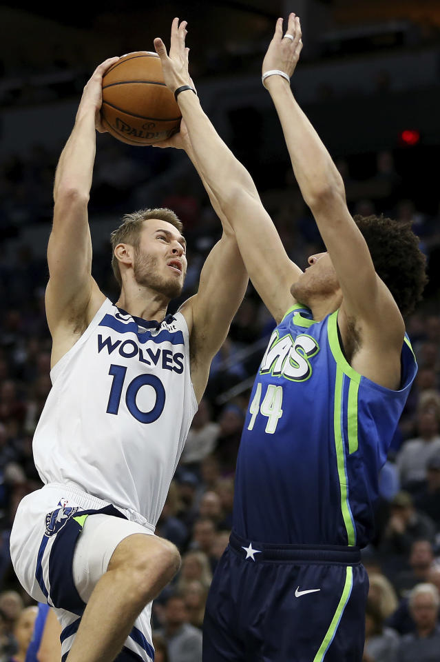 Minnesota Timberwolves' Jake Layman (10) goes up to the basket against Dallas Mavericks' Justin Johnson in the first half of an NBA basketball game Sunday, March 1, 2020, in Minneapolis. (AP Photo/Stacy Bengs)