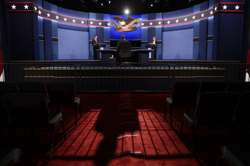 The moderator casts a long shadow as students stand in for the candidates during a rehearsal Tuesday, Oct. 18, 2016 for the third presidential debate between Republican presidential nominee Donald Trump and Democratic presidential nominee Hillary Clinton at UNLV in Las Vegas. (AP Photo/John Locher)