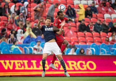 Sep 13, 2015; Toronto, Ontario, CAN; Toronto FC forward Robbie Findley (55) jumps for a ball with New England Revolution defender Chris Tierney (8) during the first half in a game at BMO Field. The New England Revolution won 3-1. Mandatory Credit: Nick Turchiaro-USA TODAY Sports