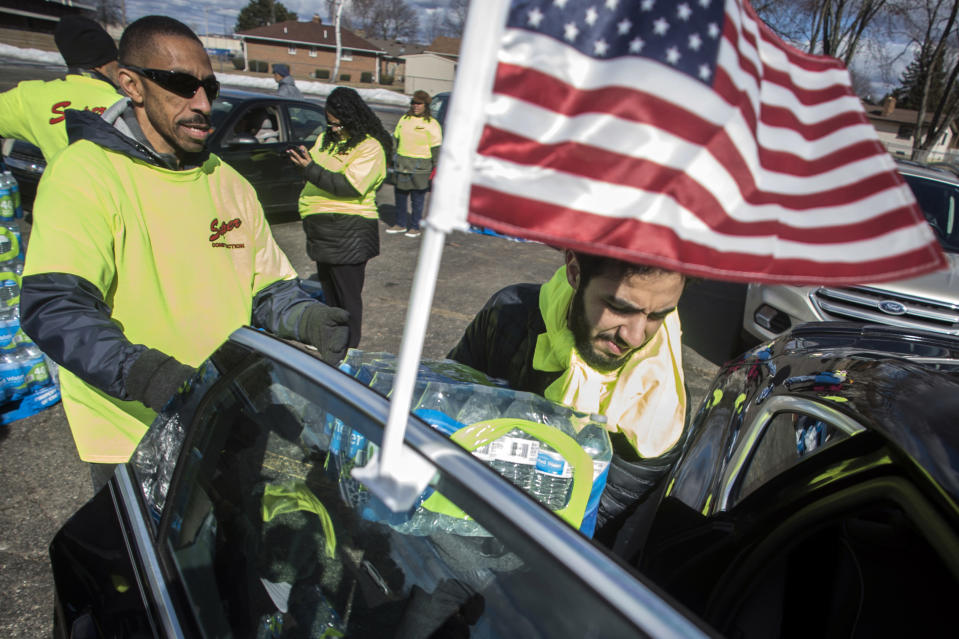 FILE - Flint resident Mohammed Busaqir loads a fellow resident's vehicle with cases of free bottled water during World Water Day on Friday, March 22, 2019 in Flint. A judge granted preliminary approval Thursday, Jan. 21, 2021 to a $641 million deal that would benefit Flint residents who were harmed by lead-contaminated water. The settlement includes $600 million from the state of Michigan, although Flint, an area hospital and an engineering firm are also part of the agreement. (Jake May/The Flint Journal via AP)