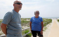 Rick Bertsch, left, and Susan Cox, right, discuss three wind energy projects that have been approved for the ocean off the coast of Ocean City, N.J., where they are standing on July 8, 2021. They oppose the projects on numerous grounds, including visual pollution, and worries about added costs and unknown impacts on the ocean and the environment. (AP Photo/Wayne Parry)