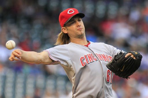 Cincinnati Reds starting pitcher Bronson Arroyo (61) throws out Colorado Rockies' Dexter Fowler at first during the first inning of a baseball game on Friday, July 27, 2012, in Denver. (AP Photo/Barry Gutierrez)