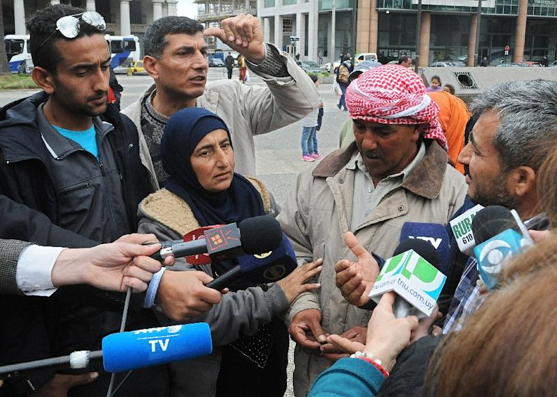 Syrian refugees speak to the press as they demonstrate at Independence Square in Montevideo on September 7, 2015 (AFP Photo/Miguel Rojo)