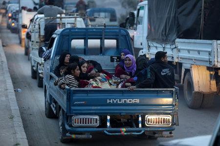 Kurdish civilians sit at the back of a truck in Afrin, Syria March 18, 2018. REUTERS/Khalil Ashawi