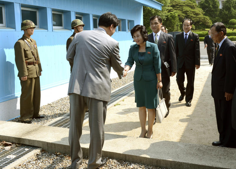 """In this photo released by the South Korean Unification Ministry, Kim Song Hye, center, the head of North Korea's delegation, shakes hands with an unidentified South Korean officer before crossing a military demarcation line, which has separated the two Koreas since the Korean War, for a meeting with South Korean delegates at Panmunjom in Paju, north of Seoul, South Korea, Sunday, June 9, 2013. Government delegates from North and South Korea began preparatory talks Sunday at the """"truce village"""" on their heavily armed border aimed at setting ground rules for a higher-level discussion on easing animosity and restoring stalled rapprochement projects. (AP Photo/South Korean Unification Ministry, HO)"""