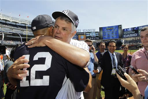 Former New York Yankees manager Lou Piniella, second from left, embraces Yankees relief pitcher Mariano Rivera (42) before the Old Timers Day baseball game on Sunday, June 23, 2013, in New York. (AP Photo/Kathy Willens)