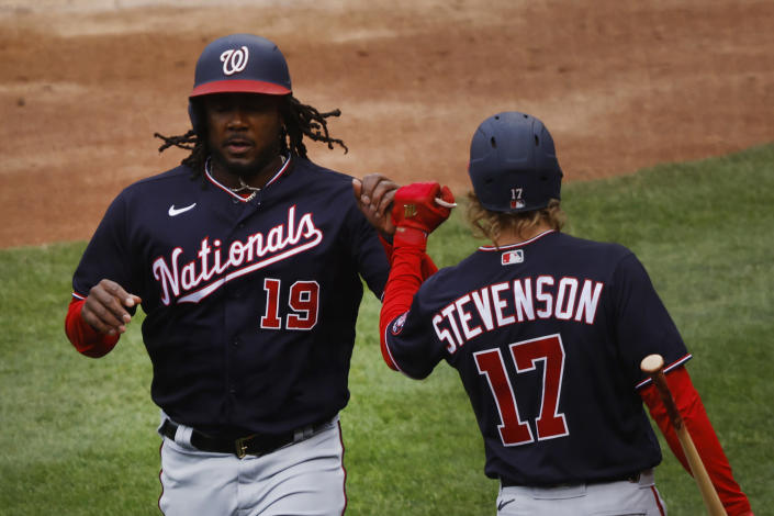 Washington Nationals' Josh Bell celebrates with Andrew Stevenson after scoring on a single by Starlin Castro during the third inning of the team's baseball game against the New York Mets, Saturday, April 24, 2021, in New York. (AP Photo/Jason DeCrow)