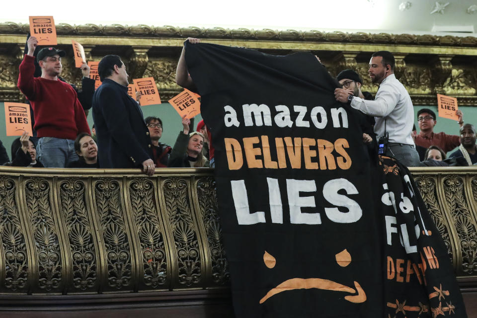 NEW YORK, NY - JANUARY 30: Protestors unfurl anti-Amazon banners from the balcony of a hearing room during a New York City Council Finance Committee hearing titled 'Amazon HQ2  Stage 2: Does the Amazon Deal Deliver for New York City Residents?' at New York City Hall, January 30, 2019 in New York City. Some Queens community members and activists say Amazon's move to Queens will further gentrify neighborhoods in the area and add more stress to an already struggling infrastructure system. (Photo by Drew Angerer/Getty Images)