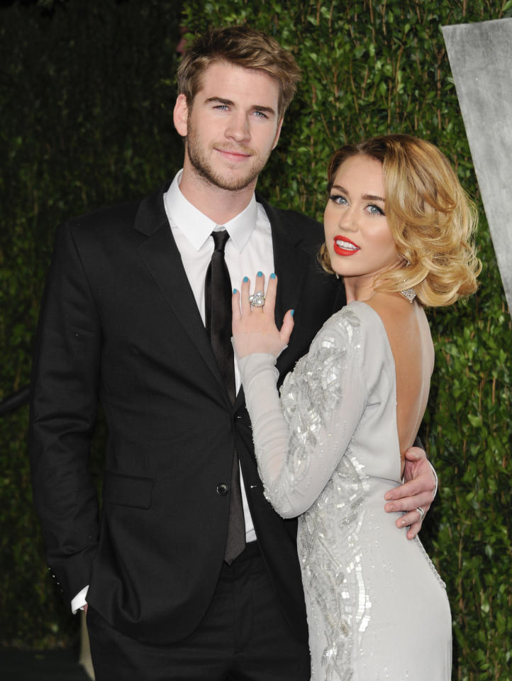 "FILE - This Feb. 26, 2012 file photo shows Miley Cyrus, right, and Liam Hemsworth at the Vanity Fair Oscar party in West Hollywood, Calif. The couple who met on the set of the movie ""The Last Song"" in 2009 announced their engagement Wednesday morning. Publicist Jeff Raymond confirms a People Magazine report of the news. Hemsworth, the 22-year-old Australian star of ""The Hunger Games,"" and Cyrus, the 19-year-old ""Hannah Montana"" star and singer, were engaged on May 31. Hemsworth proposed with a 3.5-carat diamond ring, People reports. (AP Photo/Evan Agostini, file)"
