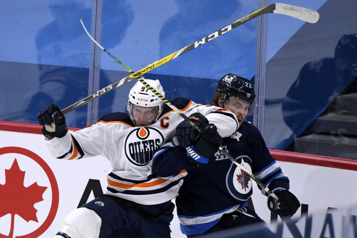 Winnipeg Jets' Mason Appleton (22) collides with Edmonton Oilers' Connor McDavid (97) during the first period of an NHL hockey game Tuesday, Jan. 26, 2021, in Winnipeg, Manitoba. (Fred Greenslade/The Canadian Press via AP)