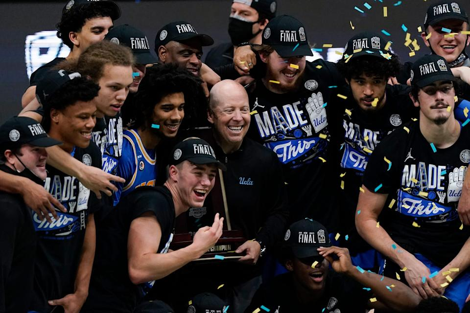 UCLA coach Mick Cronin, center, celebrates with his team after an Elite 8 win against Michigan in the NCAA men's college basketball tournament.