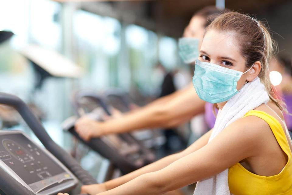 Group of people doing fitness in a gym wearing a mask, coronavirus concept
