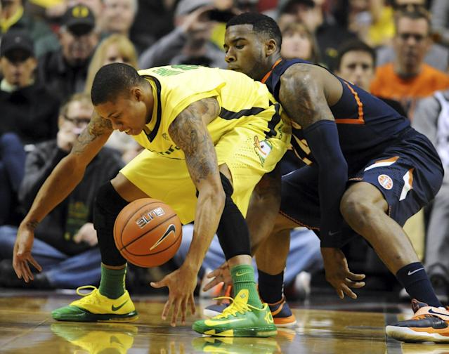 Oregon guard Joseph Young, left, and Illinois guard Rayvonte Rice scramble for a loose ball during the first half of an NCAA college basketball game in Portland, Or., Saturday, Dec. 14, 2013. (AP Photo/Steve Dykes)