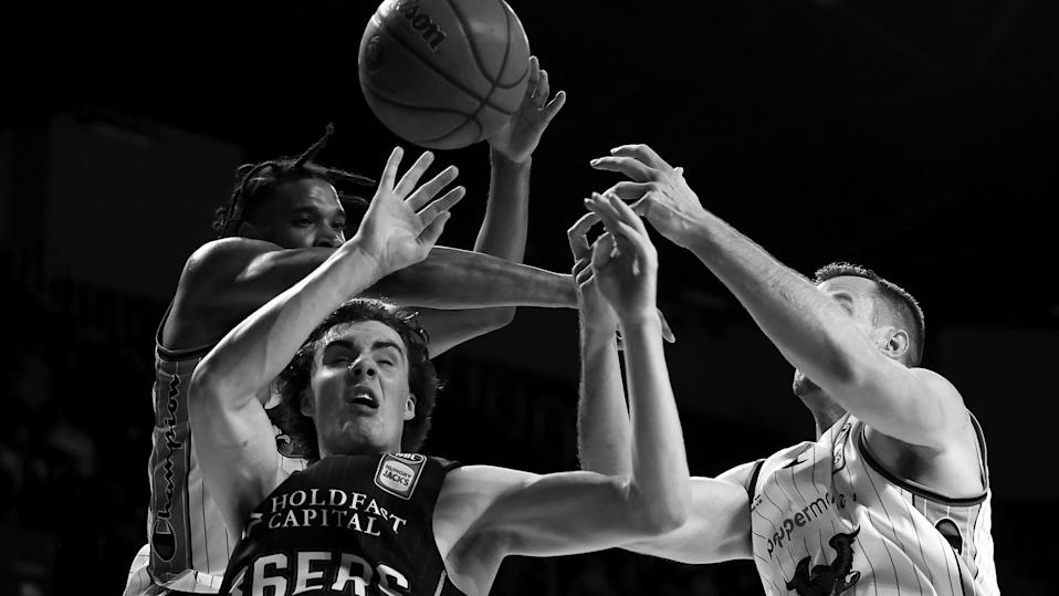 WOLLONGONG, AUSTRALIA - MAY 11:  (EDITORS NOTE: Image has been converted to black and white.) Josh Giddey of the 36ers competes for the ball with Justin Simon and AJ Ogilvy of the Hawks  during the round 18 NBL match between the Illawarra Hawks and Adelaide 36ers at WIN Entertainment Centre, on May 11, 2021, in Wollongong, Australia. (Photo by Mark Kolbe/Getty Images) ORG XMIT: 775644797 ORIG FILE ID: 1317432450