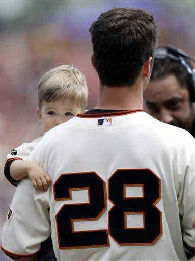 San Francisco Giants catcher Buster Posey holds his son Lee Dempsey as he accepts the National League MVP award before a baseball game against the St. Louis Cardinals on Saturday, April 6, 2013, in San Francisco. (AP Photo/Marcio Jose Sanchez)
