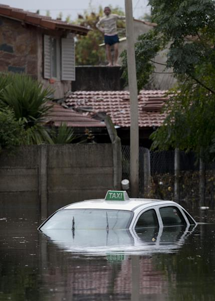 A man stands on the roof of his home above a flooded street where a taxi is submerged in La Plata, in Argentina's Buenos Aires province, Wednesday, April 3, 2013. At least 35 people were killed by flooding overnight in Argentina's Buenos Aires province, the governor said Wednesday, bringing the overall death toll from days of torrential rains to at least 41 and leaving large stretches of the provincial capital under water. (AP Photo/Natacha Pisarenko)