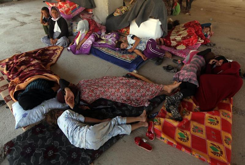 Iraqi Yazidis, who fled their homes when Islamic State militants attacked the town of Sinjar, rest in a building where they found refuge on the outskirts of the Kurdish city of Dohuk on August 16, 2014 (AFP Photo/Ahmad Al-Rubaye)