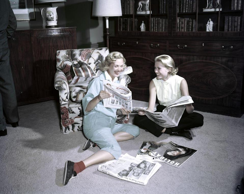 <p>In between the star's busy filming schedule—the actress released four films in 1954 alone—Kelly finds time to relax at home with a friend and read magazines. </p>